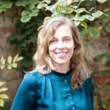 Eine junge Frau blickt gerade in die Kamera und lächelt offen. Sie hat schulterlanges dunkelblondes Haar und trägt eine petrolfarbene Bluse. Den Hintergrund bilden Blätter vor einer Hauswand.