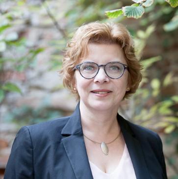 Eine Frau mit rotem welligen Haar und Kurzhaarfrisur blickt mit öeicht geöffnetem Mund in die Kamera. Sie trägt eine Brille und Ohrringe sowie eine Halskette mit Anhänger. Über einem cremefarbenem Shirt trägt sie einen dunkelblauen Blazer.