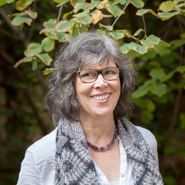 Eine Frau mit grauem, gewelltem Haar und Brille blickt leicht schräg an der Kamera vorbei aus dem Bild heraus. Sie hat sich einen graugemusterten Schal um die Schultern geschlagen, darunter eine hellgraue Bluse und eine breite dunkle Halskette. Den Hintergrund bildet Blattwerk.