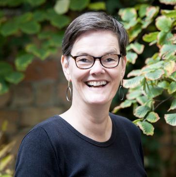 Eine Frau im schwarzen T-Shirt schaut mit weitem Lächeln in die Kamera. Sie hat dunkle kurze Haare und trägt runde Ohrringe sowie eine dunkel gerahmte Brille. Hinter ihr wachsen Pflanzen vor einer Hauswand.
