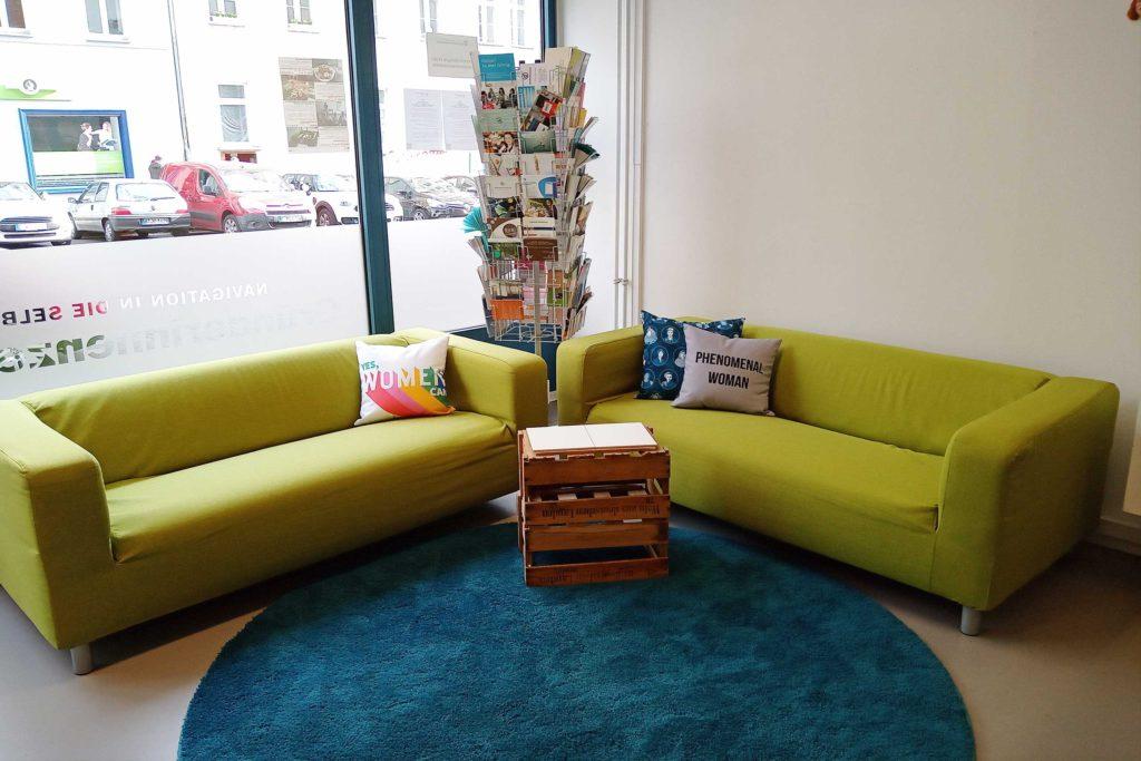 Zwei grüne Sofas in einer gemütlichen Sitzecke, dahinter ein Drehständer mit Informationsmaterial. Hier können die Teilnehmerinnen der Sofa-Gespräche platznehmen, die Gründerinnenzentrale kennenlernen und sich über Themen der Existenzgründung für Frauen informieren.