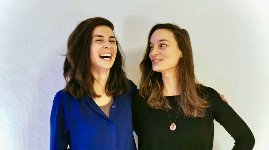 Die beiden jungen Gründerinnen Alexandra Petrikat und Marie Greive von Teethlovers stehen dicht nebeneinander vor einer weißen Wand. Beide haben lange braune Haare, die sie offen tragen. Die eine Frau trägt eine marineblaue Bluse und wirft den Kopf lachend zurück. Die andere schaut zu ihr herüber, den Arm in die Hüfte gestützt, und trägt ein schwarzes Oberteil und einen Anhänger an einer Kette.
