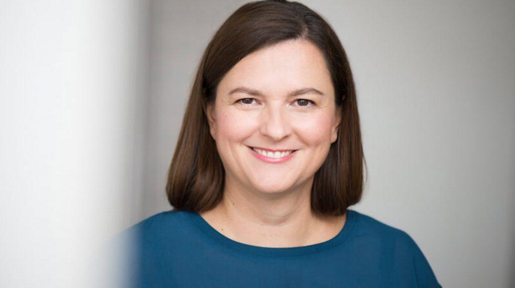 Die Gründerin Andrea Schäuble der Firma Die Freiräumerin schaut lächelnd in die Kamera. Sie hat Schulterlanges braunes Haar und trägt ein petrolfarbenes Oberteil.
