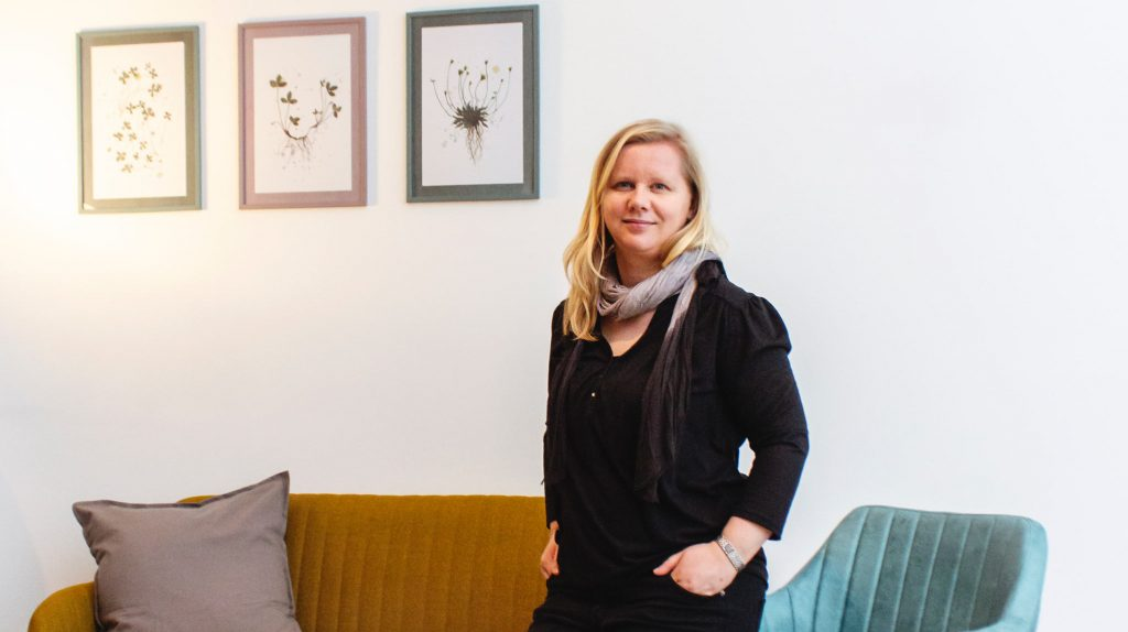 Coworking mit Kind: Die Gründerin Anne Rübsam-Rivierre von Work'n'Kid Coworking mit Kind steht in einem Wohnzimmer vor einer Couch und einem Sessel. An der Wand hängen drei Bilder. Die junge Frau ist in schwwarz gekleidet, trägt einen grauen Schal und hat längere blonde Haare.