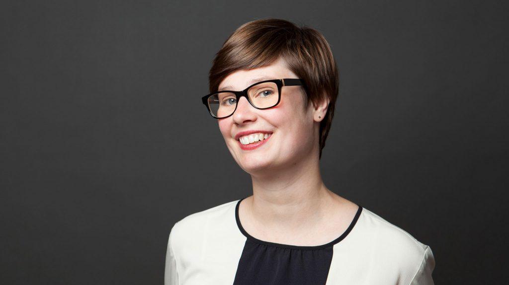 Die junge Gründerin Bianca Limbach hält ihre Kopf leicht schräg und lächelt offen. Sie trägt eine gerahmte Brille und trägt ihr braunes Haar kurz. Sie posiert vor einem dunklen Hintergrund und trägt ein helles Kostüm.