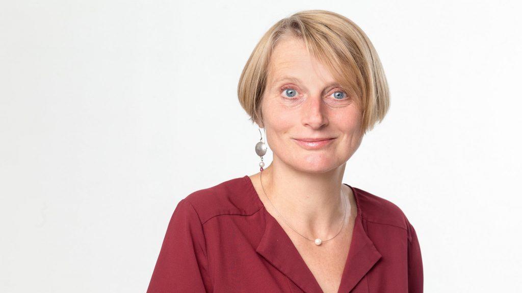 Erfolgreiche Gründerin Dr. Birgit Wolf. Eine Frau mittleren Alters mit halblangen, blonden, glatten Haaren lächelt. Sie trägt eine rote Bluse, eine dünne Kette mit einer Perle und einen großen Hängeohrring mit eine Silberscheibe.