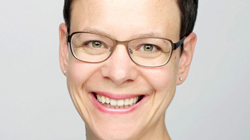 Die Unternehmerin Esther Schaefer lächelt im Close-up offen in die Kamera. Sie trägt eine Brille mit dünnem Rahmen und hat eine Kurzhaarfrisur.
