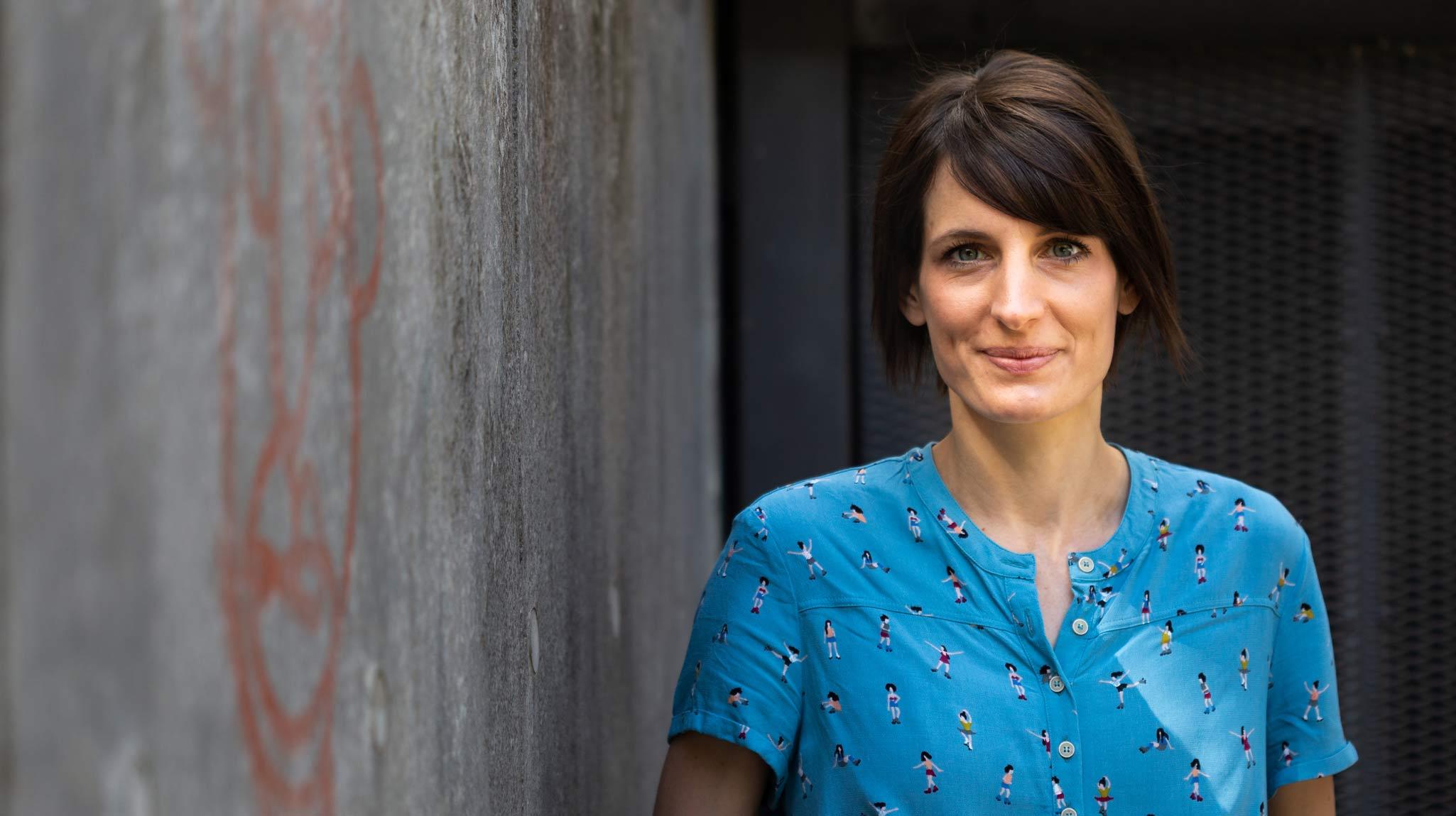 Die Unternehmerin Eva Rechau betreibt das Café no milk today. Sie lehnt an einer grauen Wand, trägt eine hellblaue Bluse und dunkelbraunes Haar.