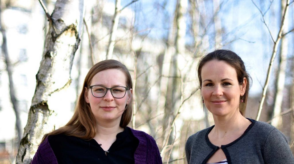 Die zwei junge Frauen von Fjordkind-Reisen blicken gemeinsam in die Kamera. Die beiden Gründerinnen von Fjordkind-Reisen, Anna Hollensteiner und Corinna Windisch, stehen vor kahlen Bäumen und blauem Himmel. Eine trägt eine Brille und ein schwarzes Oberteil. Die andere hat ihre brünetten Haare zurückgebunden und trägt eine graue Strickjacke.