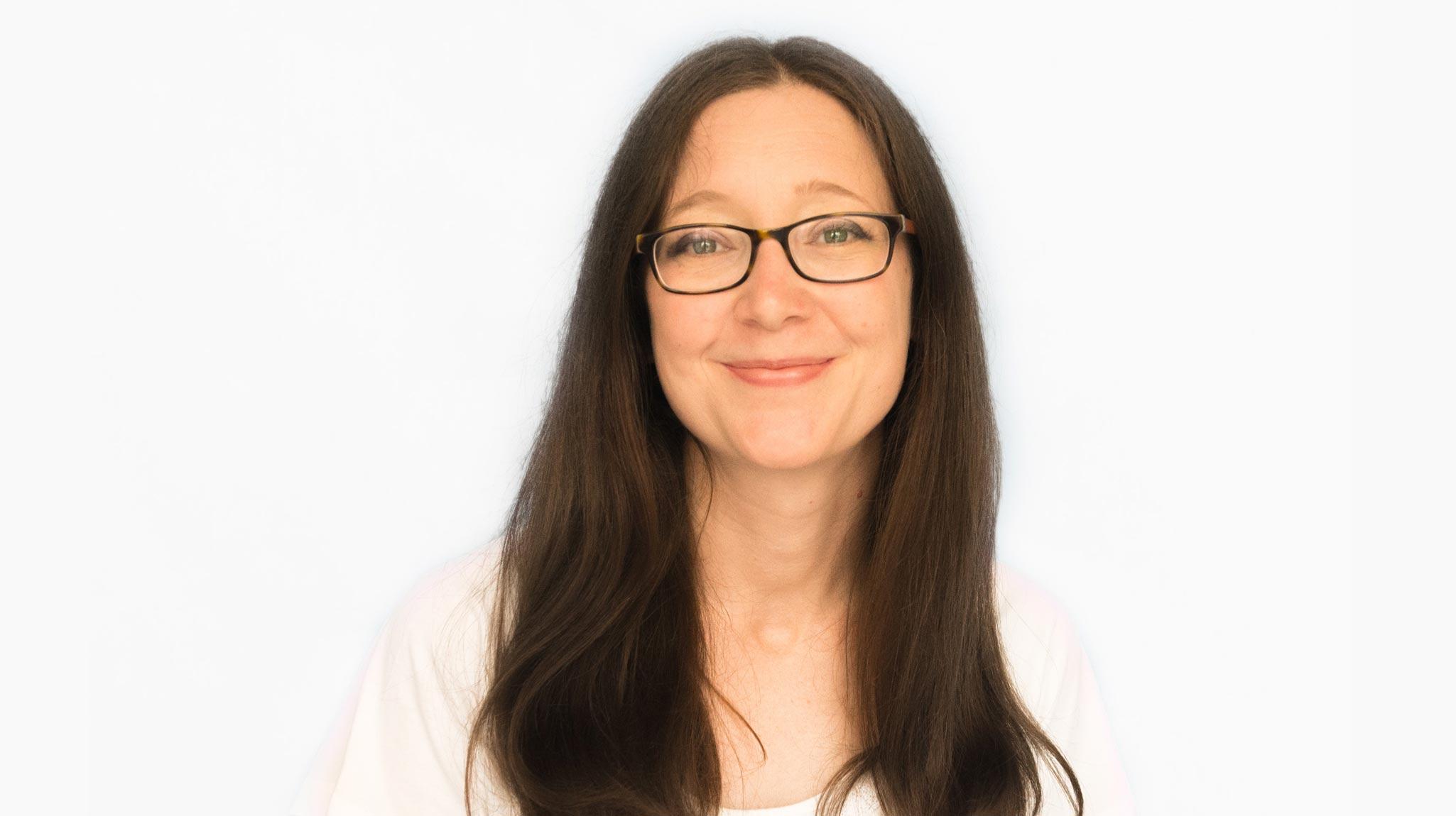 Die Unternehmerin Hannah Pehlrgimm der Praxis für Ganzheitliche Frauenheilkunde hat langes braunes Haar und trägt eine gerahmte Brille. Sie lächelt frontal in die Kamera.