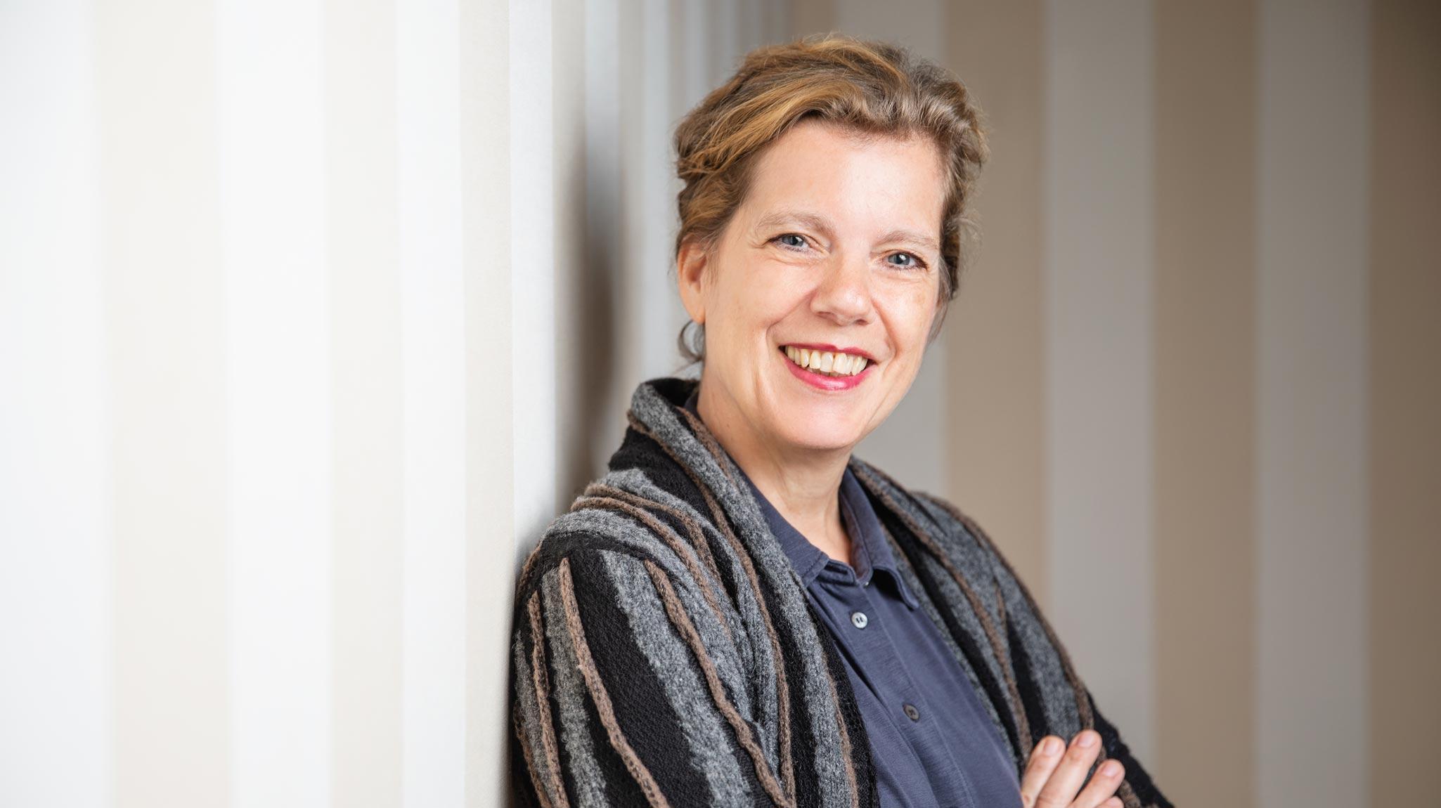 Die Gründerin Ilka Häderle von der Firma Leicht und Einfach lehnt an einer gestreift tapezierten Wand und blickt über ihre Schulter in die Kamera. Die Frau mittleren Alters lächelt offen, sie hat blonde kurze Haare und trägt eine gestreifte Strickjacke sowie eine blaue Bluse.