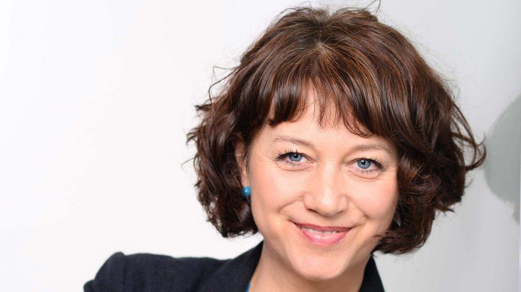 Die Gründerin Ilona Kofler von Coaching Sei hochsensibel lächelt in die Kamera. Ihr braunes Haar trägt sie in einem lockeren Kurzhaarschnitt mit Pony, dazu türkise Ohrringe.