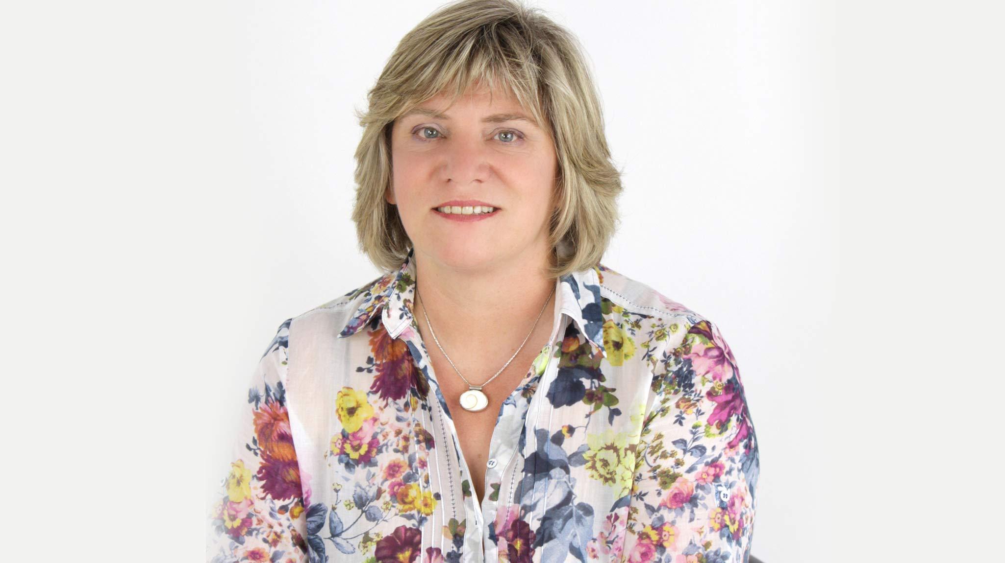 Die Gründerin Ines Külper der Firma Yorck Share blickt vor weißem Hintergrund in die Kamera und lächelt leicht. Sie trägt eine geblümte Bluse und eine Kette mit Anhänger. Ihr Haar ist mittellang und blond.