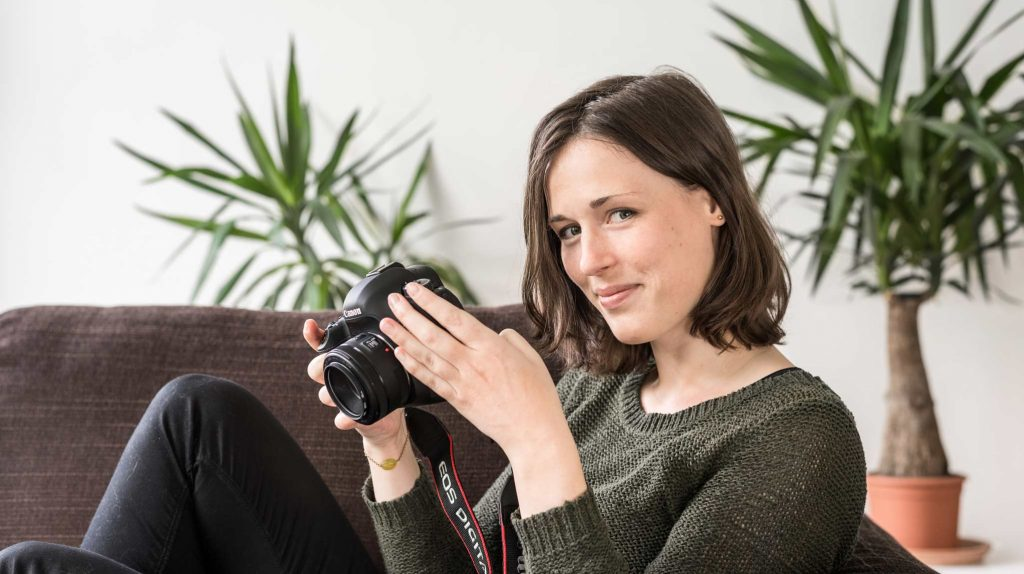 Die Gründerin Jenny Weidt der Firma Filmgrün ist eine junge Frau mit schulterlangem braunem Haar. Sie sitzt seitlich auf einem Sofa und hält einen Fotoapparat in der Hand, während sie lächelnd in die Kamera herüber blickt. Im Hintergrund stehen grüne Zimmerpflanzen.