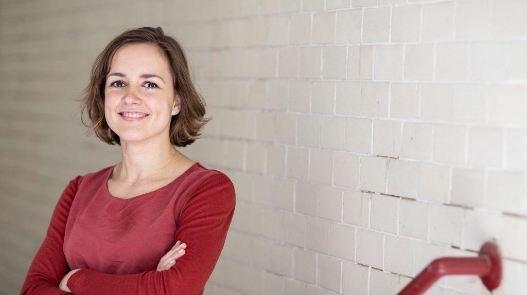 Die Gründerin der Memoiren-Manufaktur, Juliane Primus, steht vor einer weißen Ziegelwand und hält lächelnd die Arme verschränkt. Sie hat mittellange braune Haare und trägt ein rotes Oberteil.