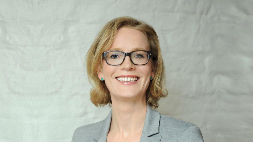 Die Gründerin und Ordnungsmentorin Katharina Vollus blickt mit offenem Lächeln in die Kamera. Sie trägt ihr blondes Haar schulterlang und trägt eine Brille und einen grauen Blazer.