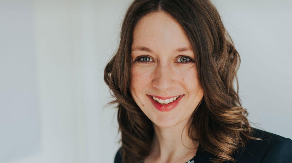 Die Gründerin Lena Hedemann schaut lächelnd in die Kamera. Sie hat langes braunes Haar in Wellen und trägt ein schwarzes Oberteil.