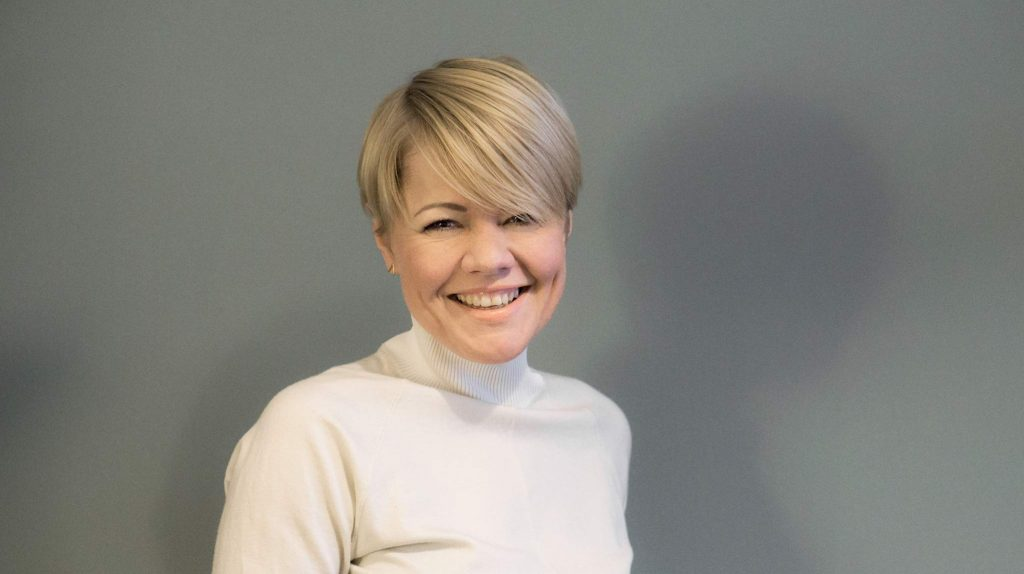 Die Gründerin Lilija Bairamova der Firma Orbasics UG steht vor einer grauen Wand und blickt lächelnd in die Kamera. Sie ist blond und hat einen Kurzhaarschnitt, sie trägt einen cremefarbenen Rollkragenpullover.