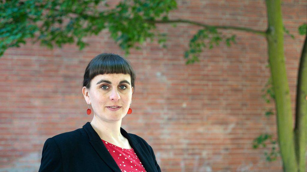 Die Gründerin Mareike Günsche der Firma The Human Perspective steht vor einer Ziegelwand und einem grünen Baum. Sie blickt in die Kamera, trägt einen Pony und rote Ohrringe, dazu einen schwarzen Blazer und ein rotes Oberteil.