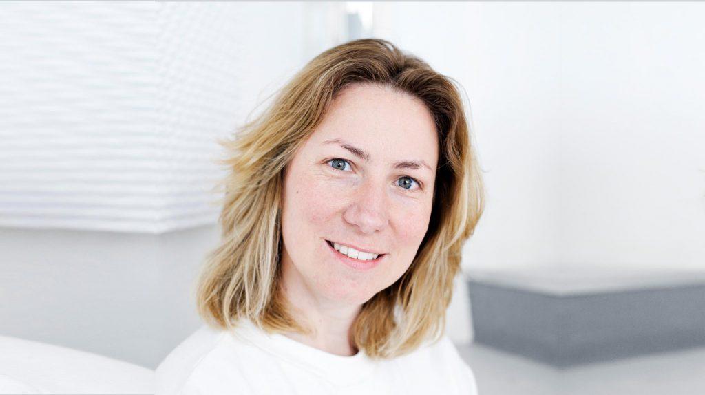 Die Gründerin von Stimme +, Marie Rodewald, hält ihren Kopf leicht schräg und lächelt in die Kamera. Sie hat blondes mittellanges Haar und trägt ein weißes Oberteil.