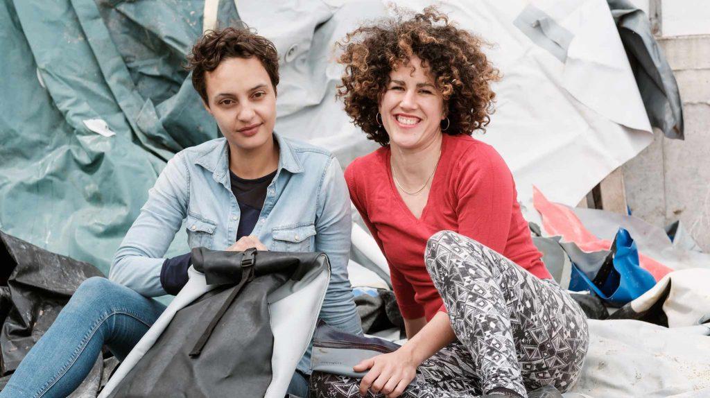 Die Gründerinnen Nora Azzaoui und Vera Günther sitzen nebeneinander vor einer weiß-grauen Plane. Die eine Frau hat kurze Haare und einen dunkleren Teint. Vor ihr steht ein Rucksack. Die andere Frau trägt ein rotes Top und eine gemusterte Hose, hat lockiges Haar und lacht offen.