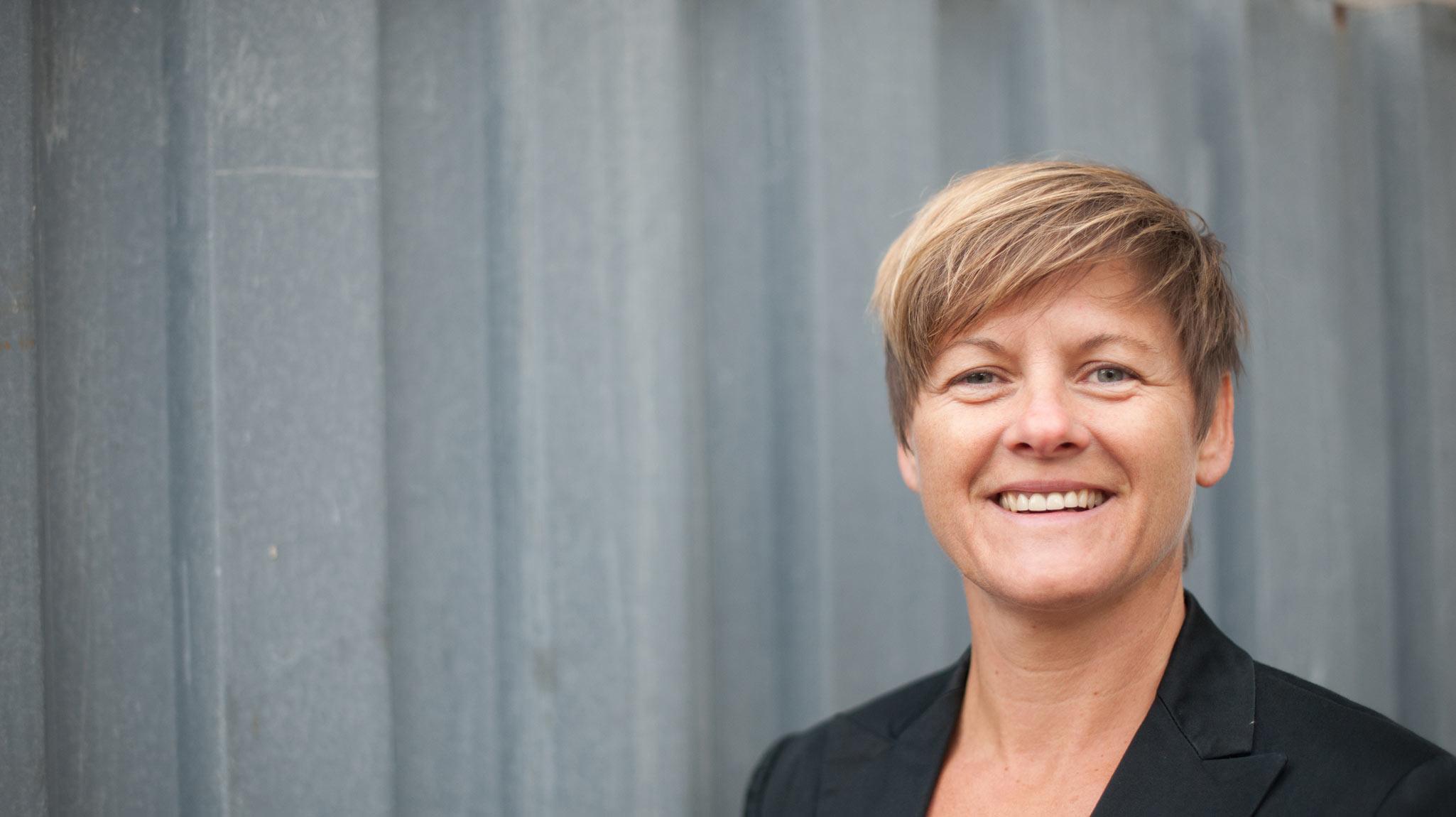 Die Unternehmerin Sabine Karko betreibt Business & Life Coaching, Mentaltraining im Sport und privaten Tanzunterricht. Sie steht vor einer grauen Wand, ist mit einem schwarzen Blazer gekleidet und schaut mit einem offenen Lächeln in die Kamera. Sie hat eine blonde Kurzhaarfrisur.