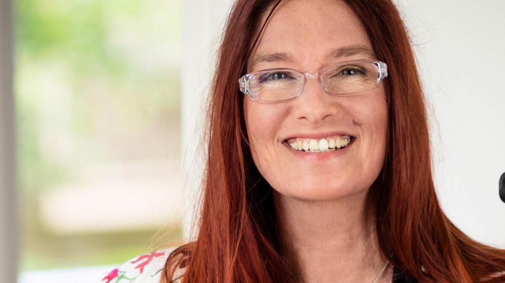 Die Gründerin Sabine Schmidt von Xaxiraxi Kleidung für jede Haut hat langes rötliches Haar und trägt eine Brille. Sie lacht offen und schaut gerade in die Kamera.