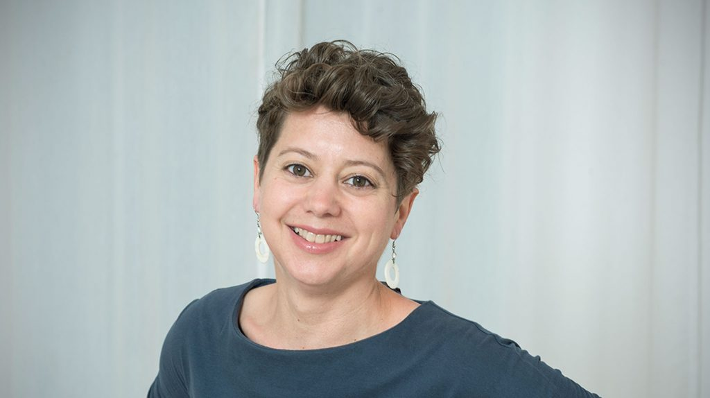 Die Gründerin der Firma Raum zum Sein Berlin, Yvonne Irle, schaut offen lächelnd in die Kamera. Ihr Kopf ist leicht geneigt. Sie hat einen Kurzhaarschnitt und trägt Ohrringe sowie ein blaues Oberteil.