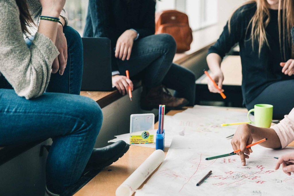 Close-up von Händen, die Stifte halten, Notizen machen und auf ein ausgebreitetes Poster zeigen: Gründerinnen versammeln sich am Tisch, beraten sich und erarbeiten ein Mindmap.