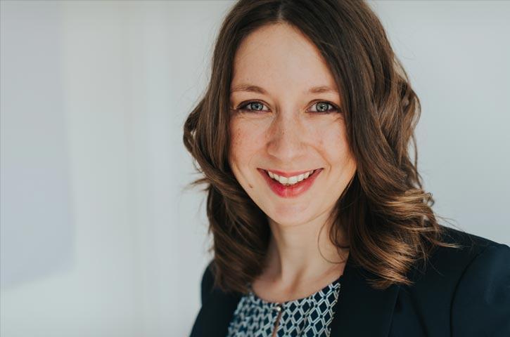 Portrait einer Gründerin, die offen in die Kamera lächelt. Sie hat längere braune Haare und trägt einen Blazer.