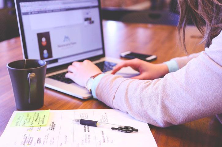 Nahaufnahme einer Frau, die am Laptop arbeitet. Ihre Hände tippen auf der Tastatur. Neben ihr auf dem Tisch steht eine Tasse Tee, daneben ein Notizbuch mit gelben Markierungen und ein Kugelschreiber.