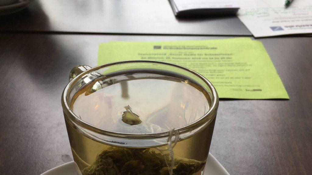 Nahansicht einer gläsernen Tasse Tee auf einer Untertasse mit einem Teebeutel. Dahinter liegt ein Flyer im hellen Grün der Gründerinnenzentrale.