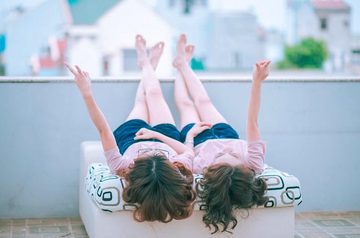 Zwei Frauen liegen auf einer Terrasse dem Rücken und heben sie Beine auf das Geländer. Beide sehen sich ähnlich, sie haben beide lockige braune Haare und tragen blaue Shorts. Sie strecken jeweils einen Arm in die Luft und blicken nach oben.