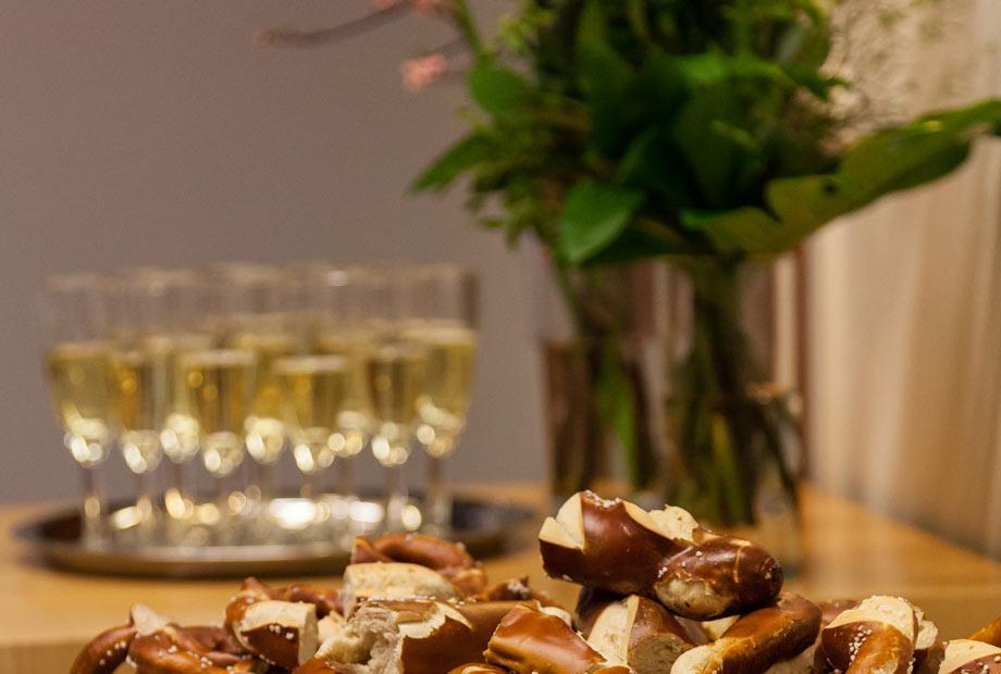 Auf einem Tisch stehen Laugengebäck und Gläser mit Sekt. Dazwischen ein Blumenstrauß in einer Vase. Für Snacks und Getränke ist gesorgt beim Netzwerkabend.