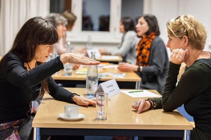 An drei hintereinander im Raum stehenden Tischen sitzen sich jeweils zwei Gründerinnen gegenüber und diskutieren. Am ersten Tisch gestikuliert eine Frau mit beiden Händen und blickt dabei ihr gegenüber an. Die Frau gegenüber stützt ihr Kinn auf der Handfläche ab und schaut konzentriert. Beide Frauen tragen schwarze Kleidung. Am zweiten Tisch sitzt eine Frau, die durch ihre orange-karierten Schal auffällt. Auch sie ist im Gespräch mit ihrer Tischpartnerin.