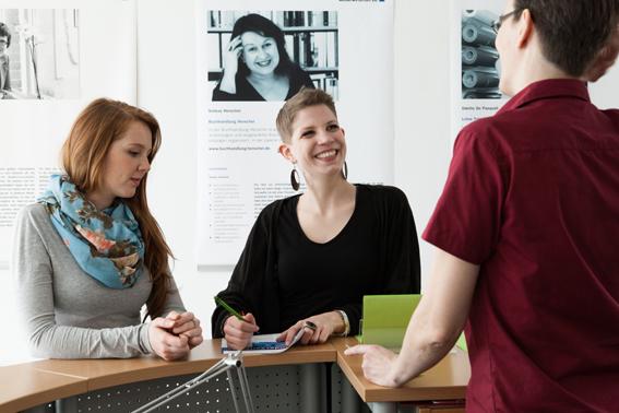 zwei junge Frauen stehen an einem Tresen und sprechen mit Frau mittleren Alters