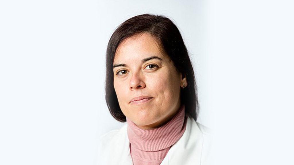 Cristina Pulido Lozano, eine mittelalte weiße Frau mit langen dunkelbrauen Haaren lächelt. Sie trägt einen Laborkittel und einen rosa Rollkragenpullover.