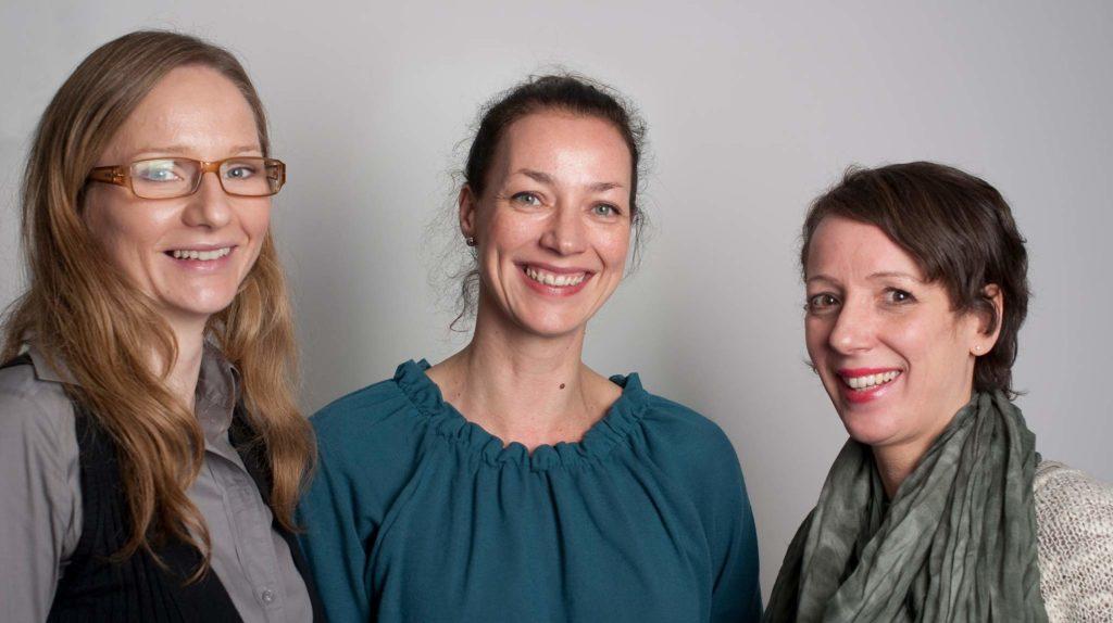 Drei Frauen, die sich zu einem Erfolgsteam zusammengetan haben, blicken lächelnd in die Kamera. Die Frau links trägt lange blonde Haare und eine Brille, die Frau in der Mitte trägt ein petrolfarbenes Oberteil und hat ihre braunenn Haare hochgebunden. Die Frau rechts hat eine Kurzhaarfrisur und hat sich einen dicken Schal um den Hals gelegt.