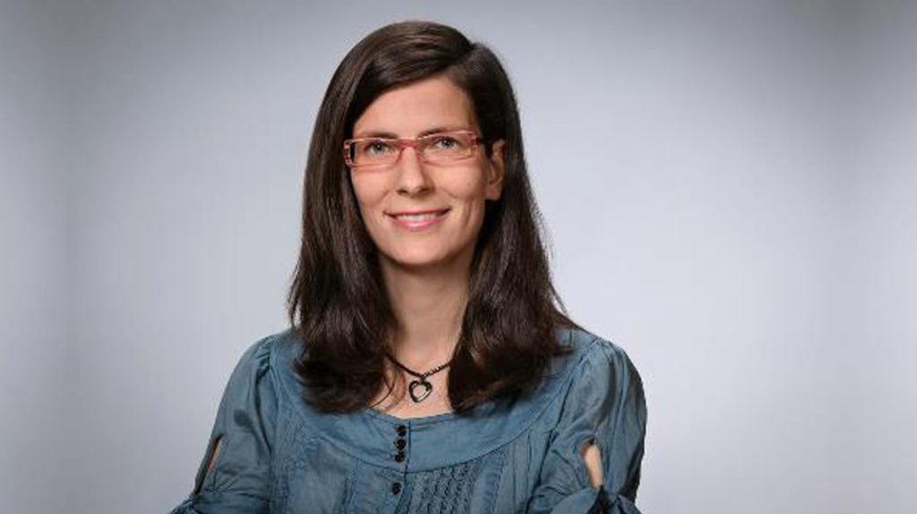 Laura Meenken, ein junge weiße Frau mit langen dunklen Haaren und Brille lächelt. Sie trägt eine blaue Bluse und eine Kette mit Herzanhänger.