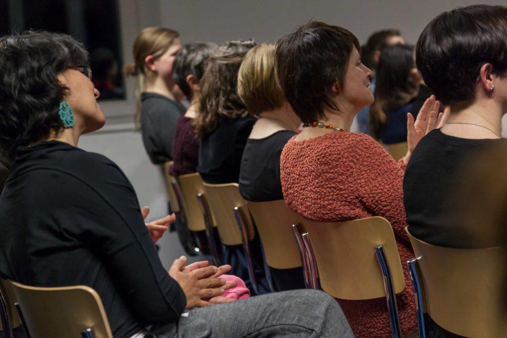 Frauen unterschiedlicher Altersgruppen sitzen Seite an Seite im Publikum bei einem Themenabend, schauen aus dem Bild heraus in Richtung Podium und applaudieren.