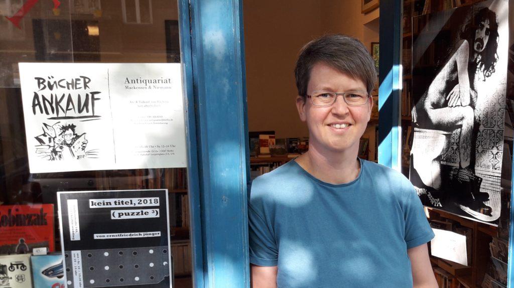 Unternehmerin Nicole Rittstieg, Frau Mitte Vierzig mit kurzen, mittelblonden Haaren steht mit T-Shirt bekleidet in der Tür ihres Antiquariats. Im Fenster hängt ein Schild mit der Aufschrift Bücher Ankauf und ein Plakat mit Frank Zappa auf Klo sitzend.
