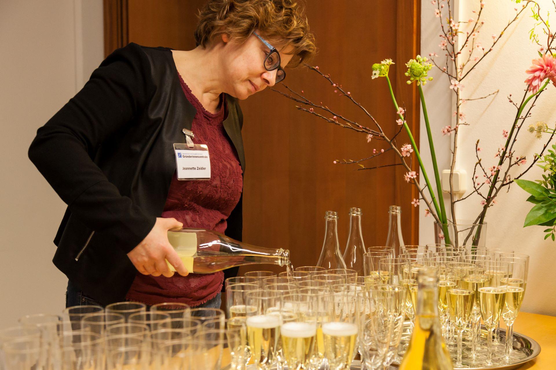 Netzwerktreffen: Eine weiße Frau mittleren Alters mit Blazer und Namensschild der Gründerinnenzentrale füllt Sektgläser aus einer Flasche.