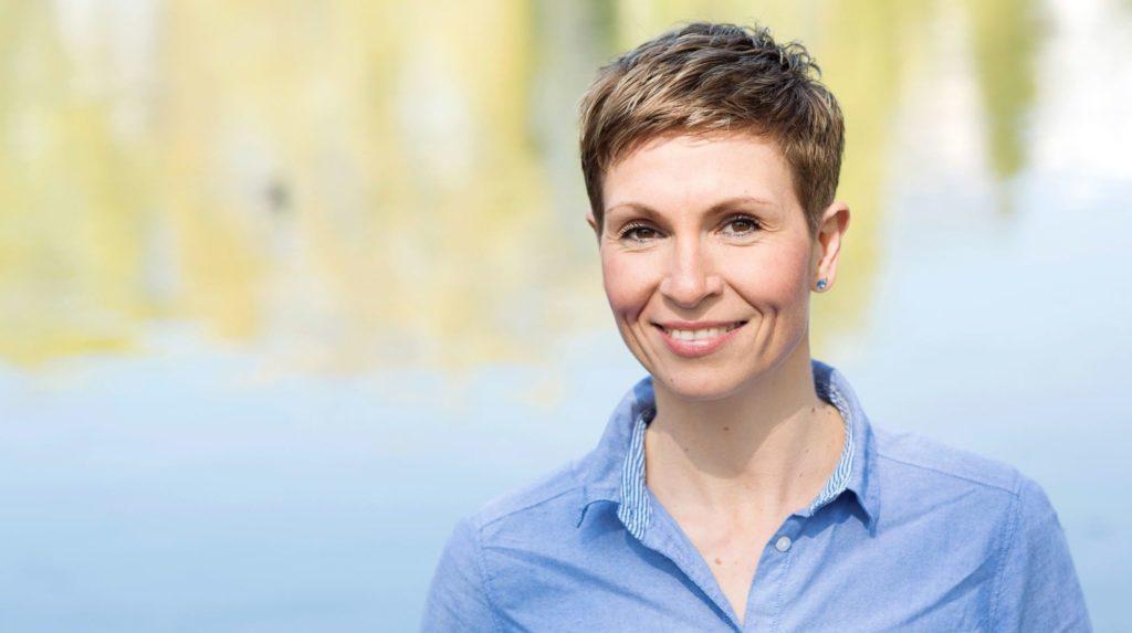 Janine Engelmann, eine weiße Frau mittleren Alters mit kurz geschnittenen mittelblonden Haaren, lächelt. Sie trägt ein legeres Jeanshemd.