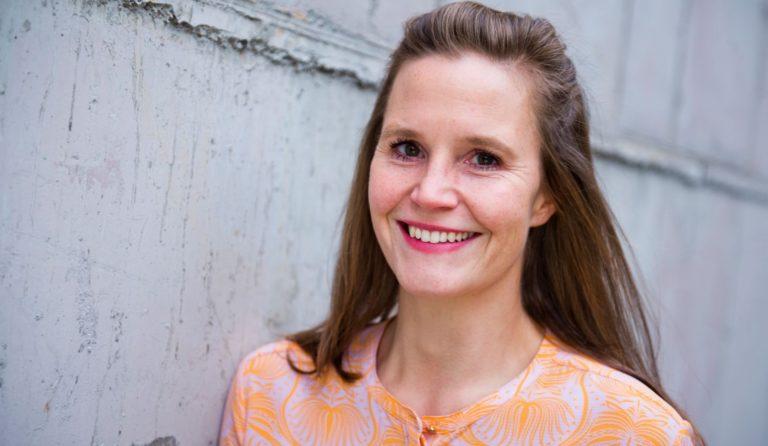Katinka Vahle, eine weiße Frau mittleren Alters mit langen, glatten, braunen Haaren, steht vor einer Mauer und lächelt in die Kamera.