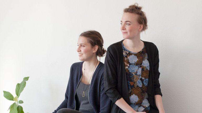 zwei junge, weiße Frauen sitzen vor einer weißen Wand und schauen links aus dem Bild. Sie tragen legere Kleidung und lächeln.