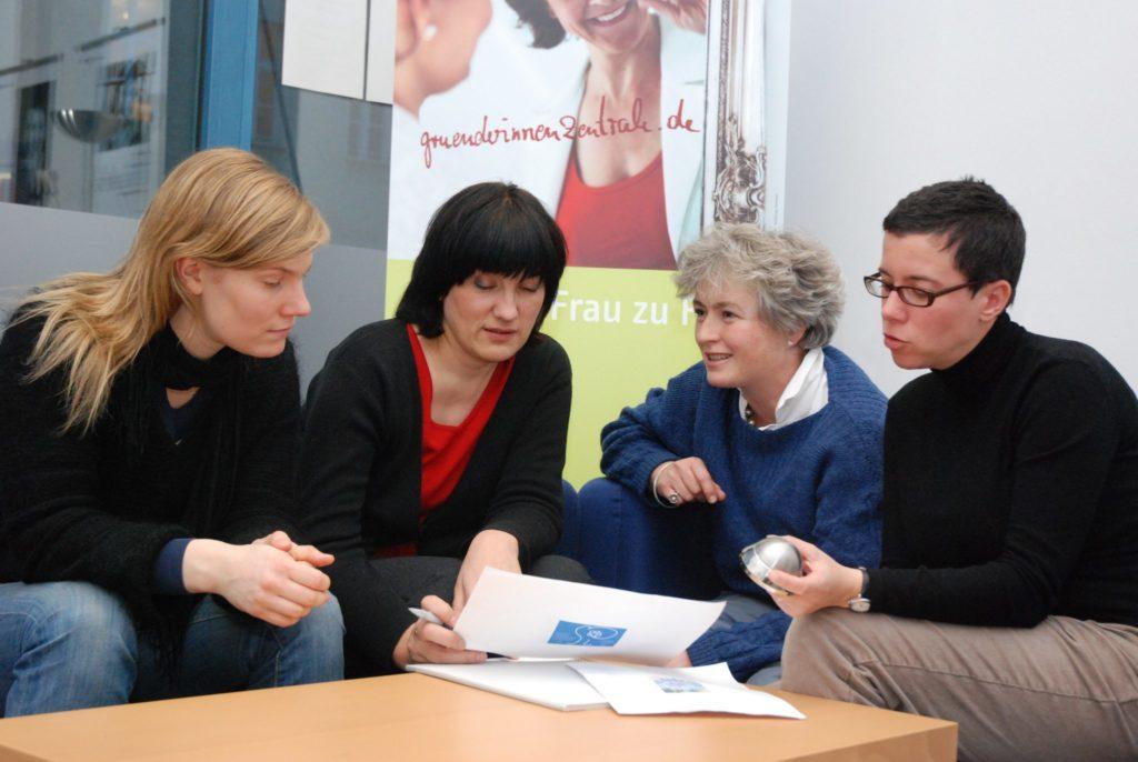 Drei Frauen informieren sich bei Mitarbeiterin der Gründerinnenzentrale zum Beratungsangebot