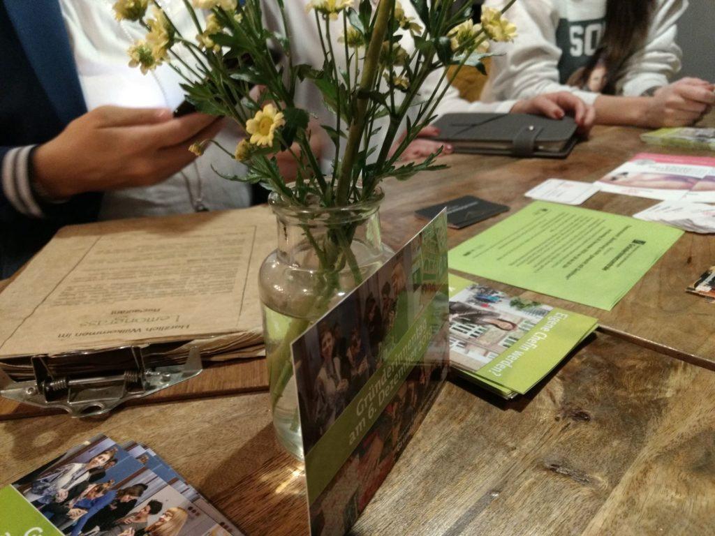 Ein Tisch mit Werbematerial, Visitenkarten und einer Speisekarte. Eine Postkarte mit Einladung zum Gründerinnentag lehnt an einer Glasvase mit Zweigen mit kleinen, gelben Blüten. Es sind Hände von drei Personen zu sehen.