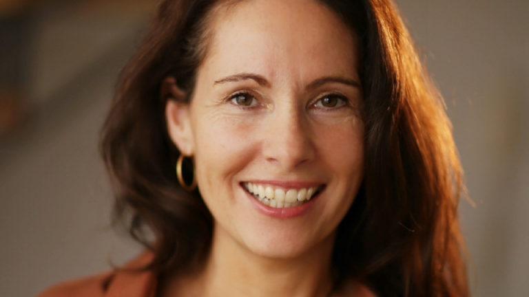 Gründerin Melanie Kleinert. Portrait einer weißen Frau mittleren Alters mit langen braunen Haaren, die von rechts von der Sonne beschienen werden. Frau Kleinert trägt goldene, mittelgroße Kreolen, lächelt mit offenem Mund und hat dabei Lachfältchen um die braunen Augen.