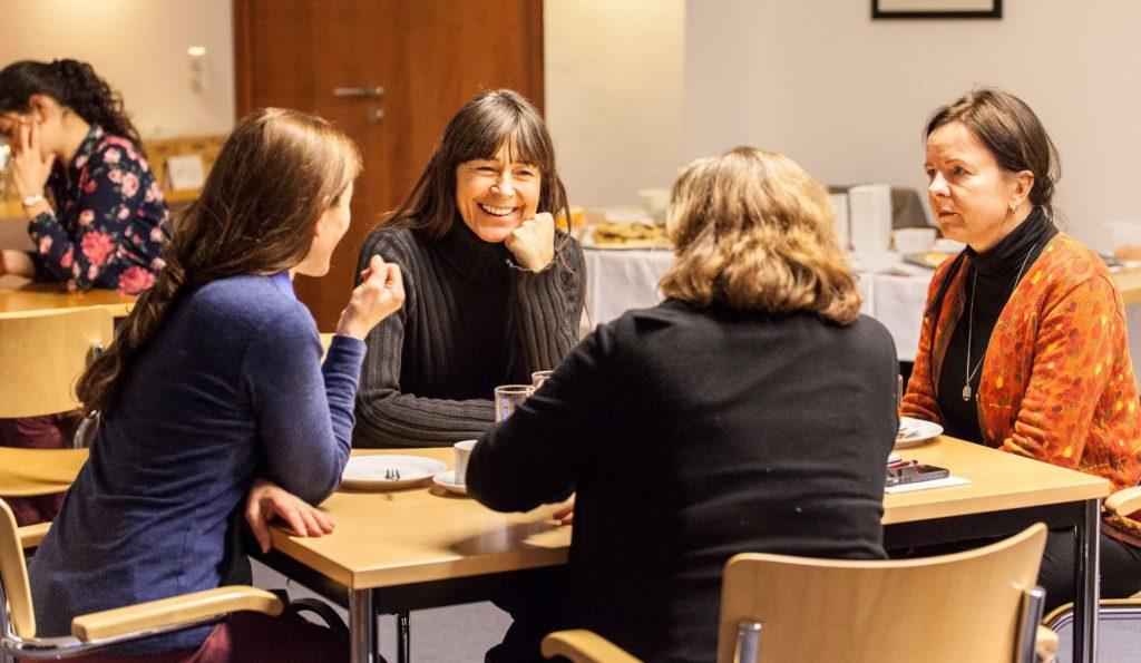 Vier weiße Frauen mittleren Alters sitzen um einen Tisch und unterhalten sich. Es stehen Kuchenteller und Kaffeetassen auf dem Tisch.