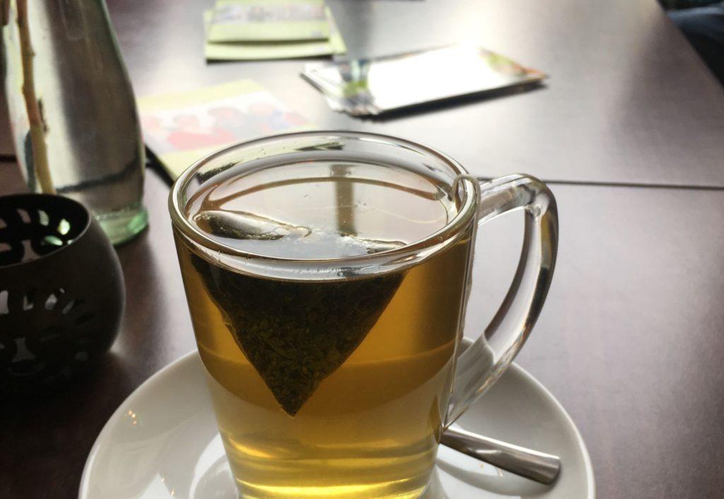 Nahansicht einer gläsernen Tasse Tee auf einer Untertasse mit einem Teebeutel. Dahinter liegen Flyer im hellen Grün der Gründerinnenzentrale.